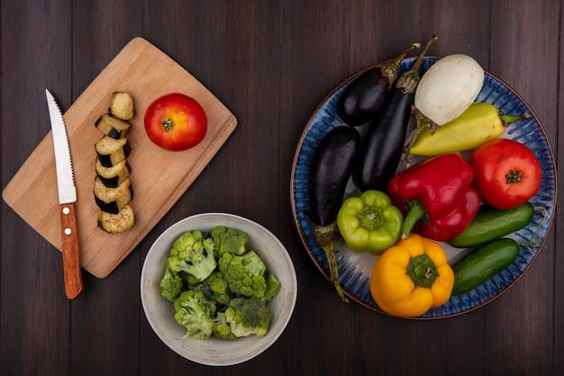 Bovenaanzicht gekleurde paprika met komkommers en tomaten aubergine op een bord en broccoli in een kom op houten achtergrond