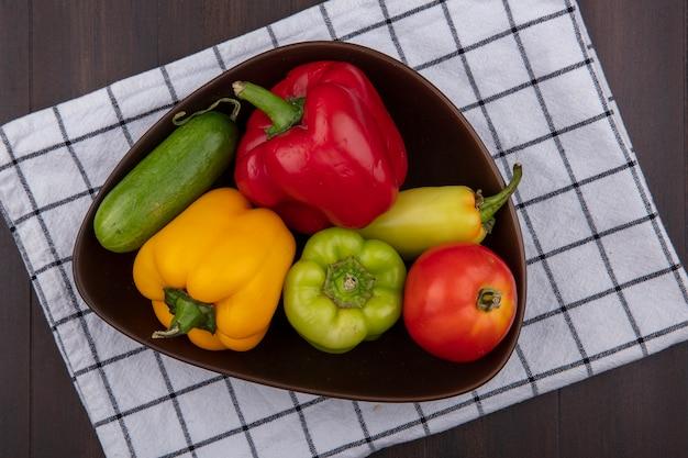 Bovenaanzicht gekleurde paprika met komkommers en tomaten in een kom op een geruite handdoek op een houten achtergrond
