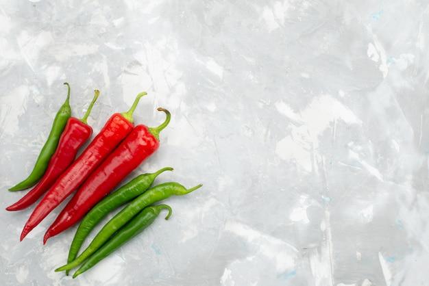 Bovenaanzicht gekleurde pikante pepers groen en rood op grijs