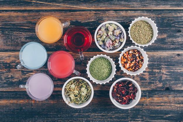 Bovenaanzicht gekleurde water en thee soorten in kopjes en kommen op donkere houten achtergrond. horizontaal