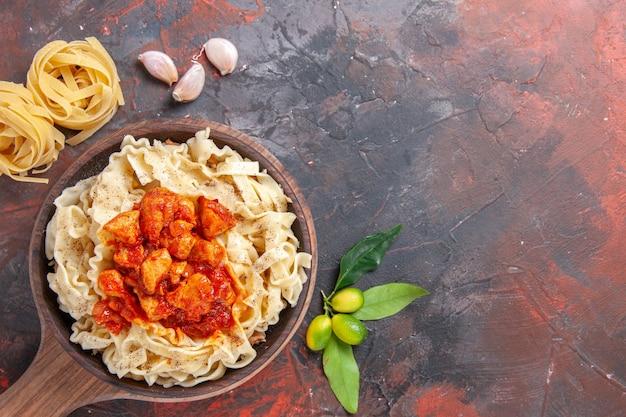 Bovenaanzicht gekookt deeg met kip en saus op de donkere ondergrond donkere pastadeegschotel