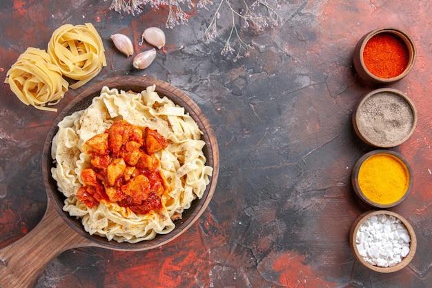 Bovenaanzicht gekookt deeg met kip en saus op donkere deeg donkere pastaschotel