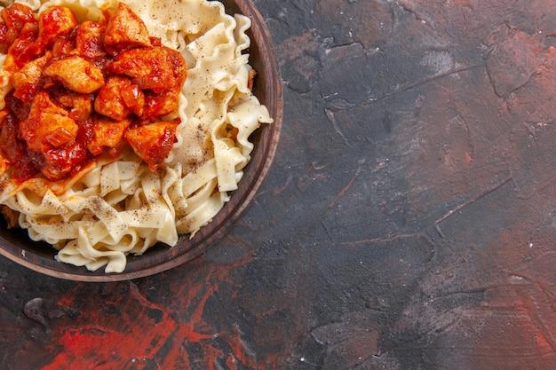 Bovenaanzicht gekookt deeg met plakjes kip en saus op donkere ondergrond pastadeeg donkere schotel