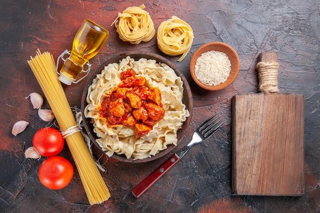 Bovenaanzicht gekookt deeg met rijst en sauced vlees op donkere ondergrond donkere pastadeegschotel