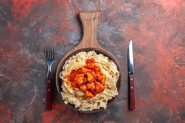 Bovenaanzicht gekookt deeg met saus vlees op donkere oppervlak deeg pastaschotel