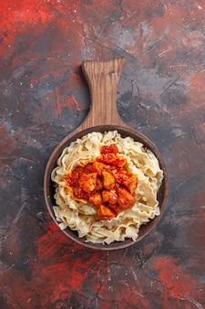 Bovenaanzicht gekookt deeg met saus vlees op een donkere deeg donkere pastaschotel