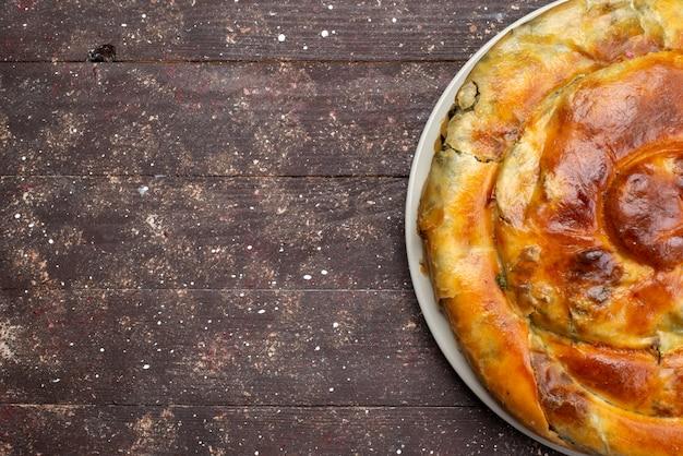 Bovenaanzicht gekookt greens gebak ronde binnen witte plaat op de bruine houten bureau maaltijd eten gebak lunch greens