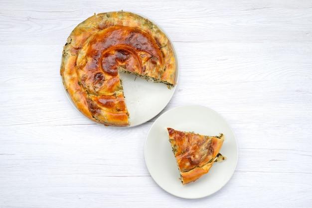 Bovenaanzicht gekookt greens gebak ronde binnen witte plaat op het heldere bureau maaltijd eten gebak lunch greens