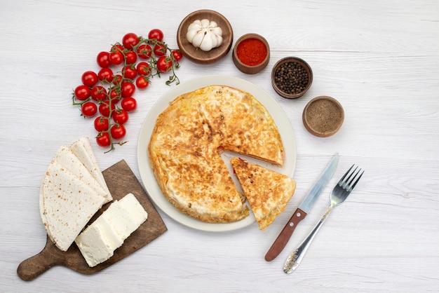 Bovenaanzicht gekookt plantaardig gebak ronde binnen witte plaat samen met witte kaas en tomaten bureau maaltijd eten gebak lunch greens