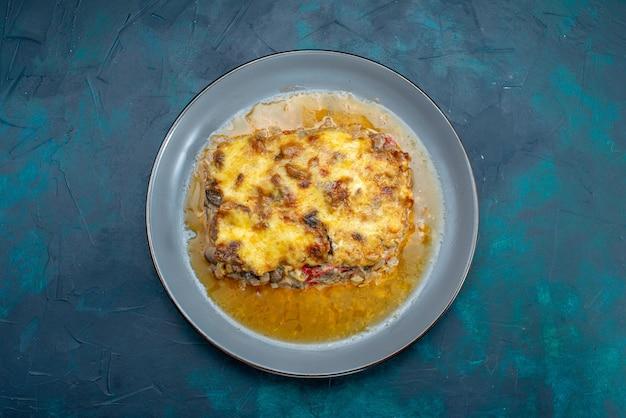 Bovenaanzicht gekookt vleesgerecht met saus en champignons in plaat op het donkerblauwe bureau vleesgerecht diner voedselmaaltijd