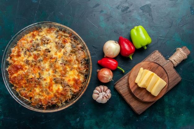 Bovenaanzicht gekookt vleesmaaltijd met gesneden vlees samen met kaas en verse groenten op donkerblauw bureau eten vleesmaaltijd gerecht diner oven bakken