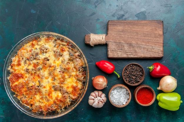 Bovenaanzicht gekookt vleesmaaltijd met gesneden vlees samen met kaas en verse groenten op donkerblauwe bureauvoedsel vleesmaaltijd schotel dineroven