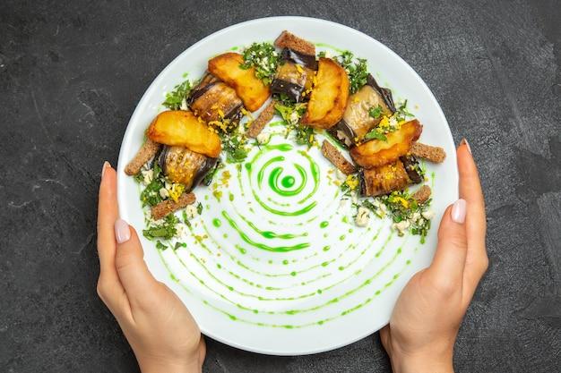 Bovenaanzicht gekookte auberginebroodjes met aardappelen in de plaat op de donkere achtergrond schotel maaltijd diner aardappel