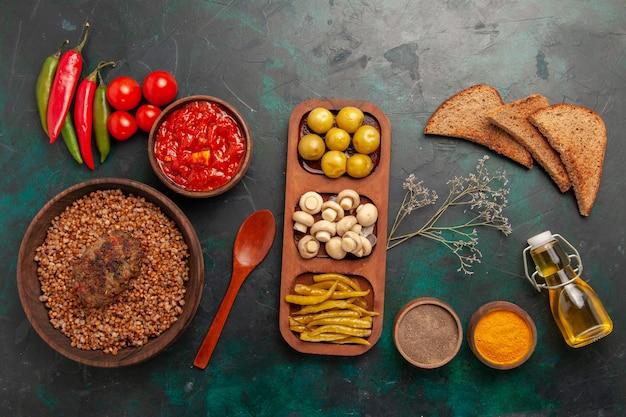 Bovenaanzicht gekookte boekweit met kotelet en tomatensaus op groen bureau