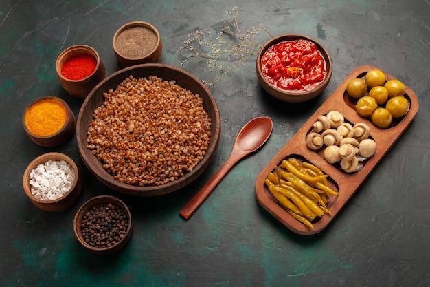 Bovenaanzicht gekookte boekweit met tomatensaus en verschillende kruiden op groene ondergrond