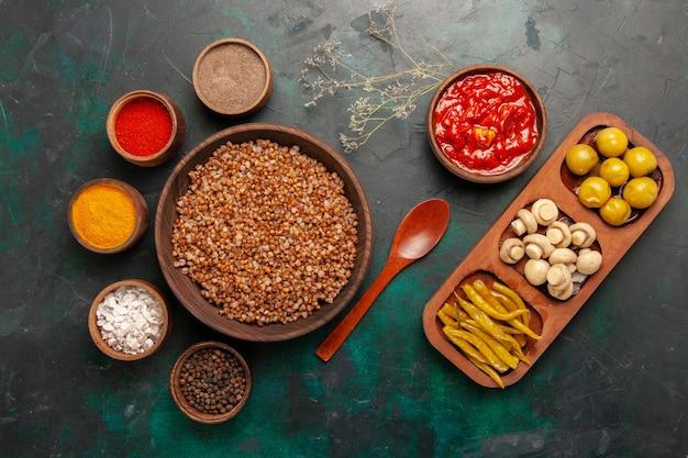 Bovenaanzicht gekookte boekweit met tomatensaus en verschillende kruiden op het donkergroene oppervlak