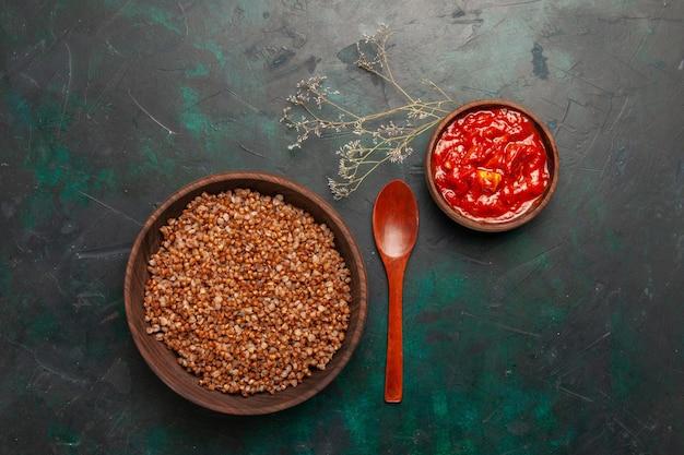Bovenaanzicht gekookte boekweit met tomatensaus op het donkergroene oppervlak