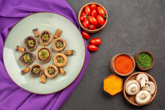 Bovenaanzicht gekookte champignons in plaat op paarse tissueschotel champignons diner kookmaaltijd