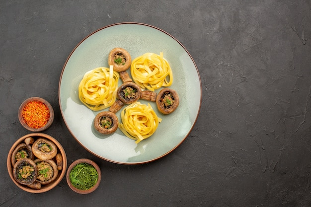 Bovenaanzicht gekookte champignons met deeg pasta op donkergrijze tafel bak eten diner maaltijd