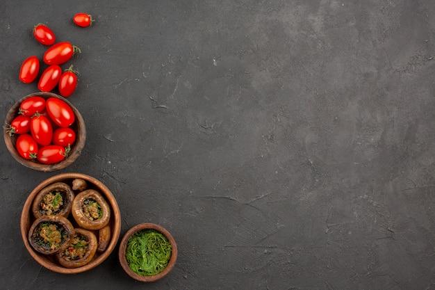 Bovenaanzicht gekookte champignons met tomaten op donkere tafel paddestoel wilde pasta