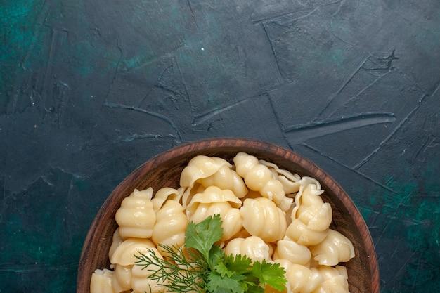 Bovenaanzicht gekookte deeg pasta met groenen binnen plaat op het donkere oppervlak