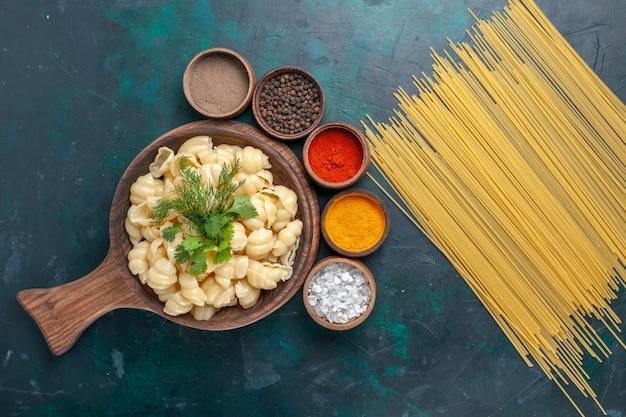 Bovenaanzicht gekookte deegpasta met verschillende kruiden op donker bureau