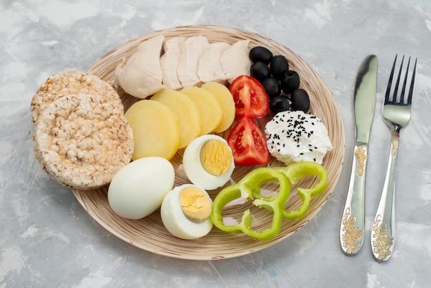 Bovenaanzicht gekookte eieren met olijven borsten kruiderijen crackers en tomaten op grijze, plantaardige maaltijd ontbijt