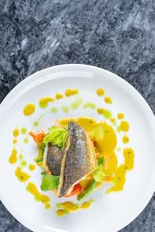 Bovenaanzicht gekookte filet zeebaars met groene saus en groenten op marmeren tafel.