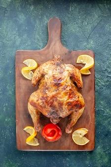 Bovenaanzicht gekookte gekruide kip met citroen op donkere ondergrond