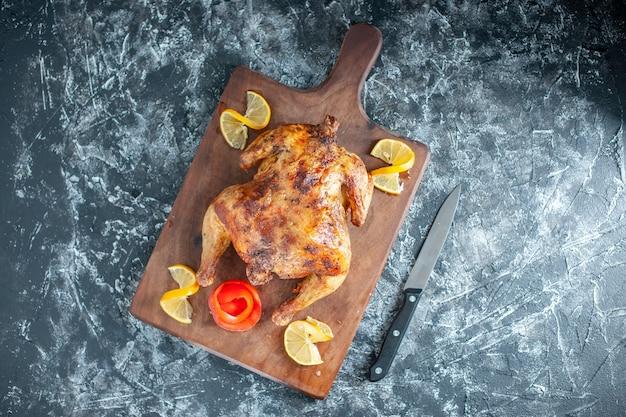 Bovenaanzicht gekookte gekruide kip met citroen op lichtgrijze ondergrond