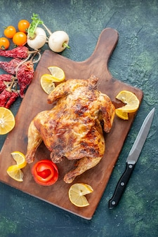 Bovenaanzicht gekookte gekruide kip met schijfjes citroen op donkere ondergrond
