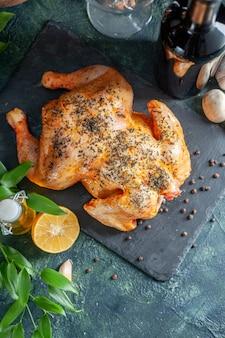 Bovenaanzicht gekookte gekruide kip met wijn en knoflook op donkere ondergrond
