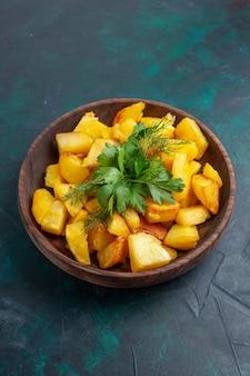Bovenaanzicht gekookte gesneden aardappelen met greens in bruine plaat op het donkerblauwe bureau