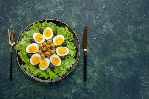 Bovenaanzicht gekookte gesneden eieren met olijven en groene salade op donkerblauwe achtergrond