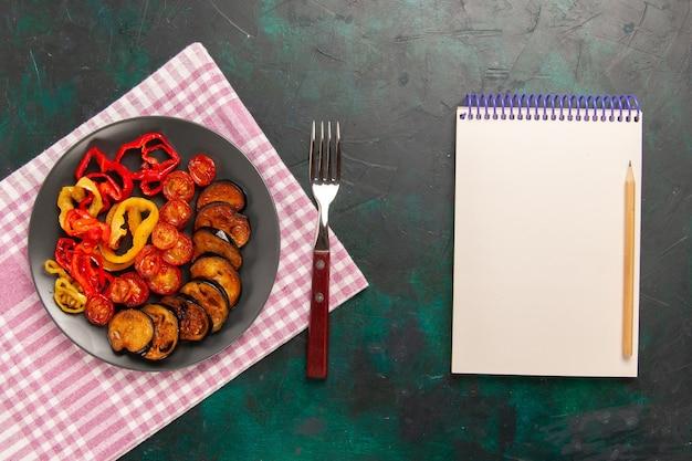 Bovenaanzicht gekookte gesneden groenten paprika en aubergines met blocnote op donkergroen oppervlak