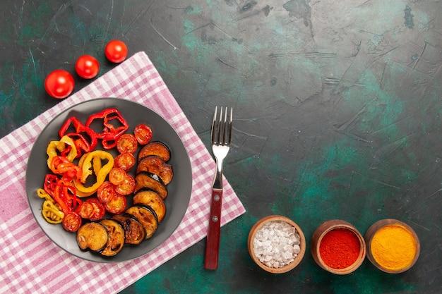 Bovenaanzicht gekookte gesneden groenten paprika en aubergines met kruiden op het groene oppervlak