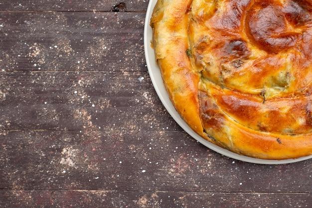 Bovenaanzicht gekookte greens gebak ronde binnen witte plaat op de bruine houten bureau maaltijd gebak lunch greens