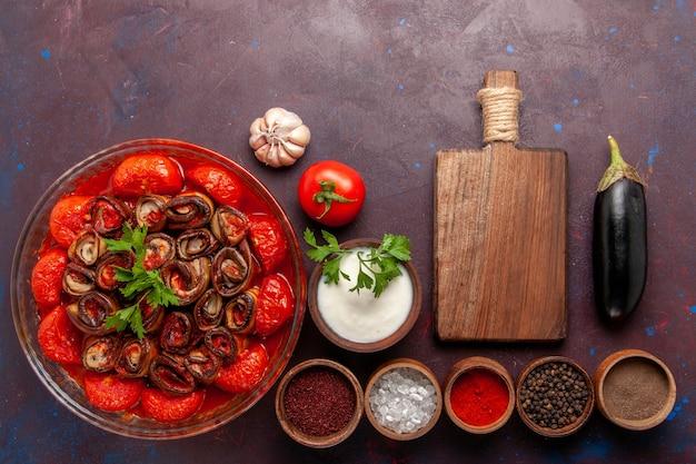 Bovenaanzicht gekookte groentemaaltijd heerlijke tomaten en aubergines met kruiden op het donkere bureau