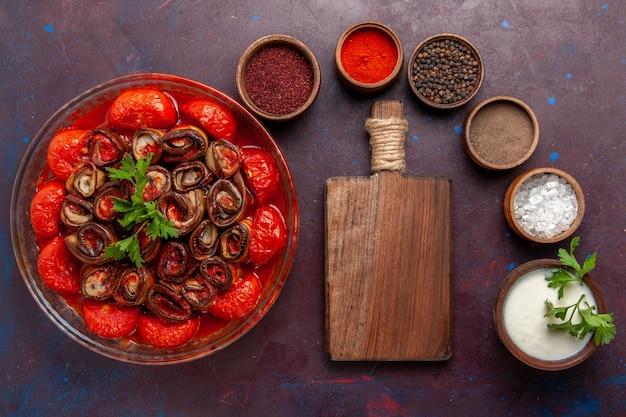 Bovenaanzicht gekookte groentemaaltijd heerlijke tomaten en aubergines met kruiden op het donkere oppervlak