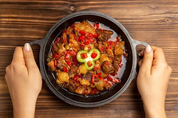 Bovenaanzicht gekookte groentemaaltijd in pan op het bruine bureau