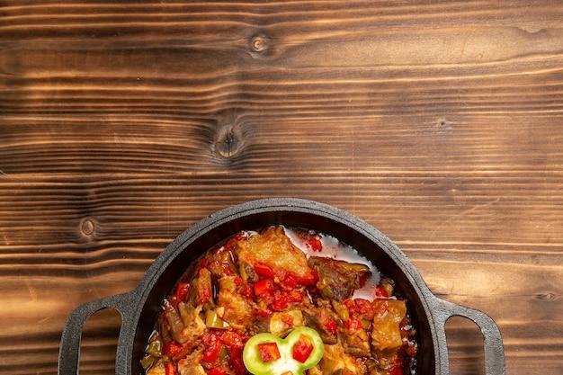 Bovenaanzicht gekookte groentemaaltijd in pan op houten bureau