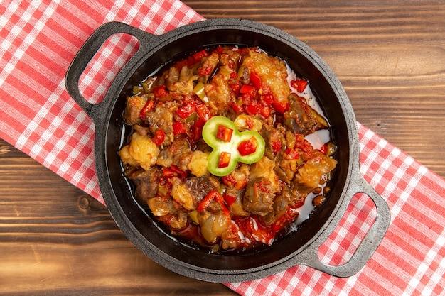 Bovenaanzicht gekookte groentemaaltijd inclusief groenten en vlees binnen op houten bruin bureau
