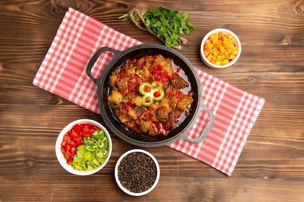 Bovenaanzicht gekookte groentemaaltijd inclusief groentesaus en vlees binnen op bruin bureau