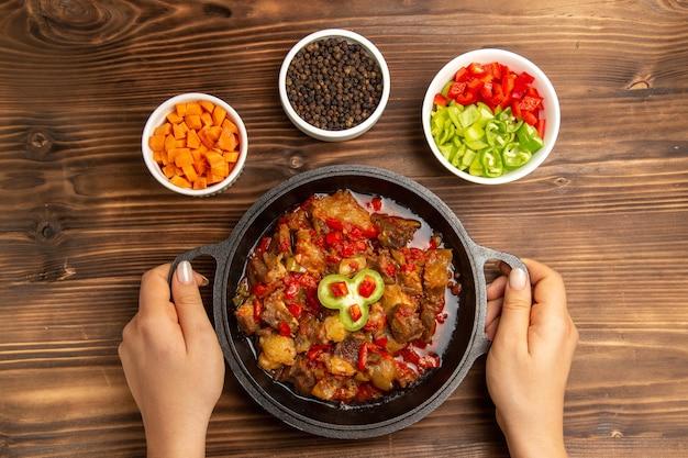 Bovenaanzicht gekookte groentemaaltijd met kruiden en gesneden peper op het houten bruine bureau