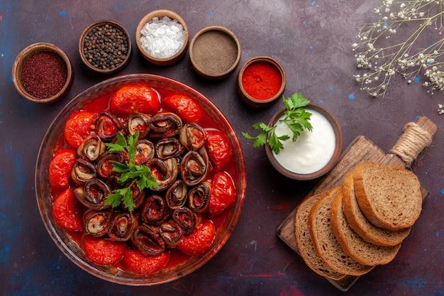 Bovenaanzicht gekookte groentemaaltijd tomaten en aubergines met broodbroodjes op donker bureau