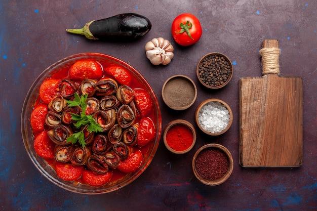 Bovenaanzicht gekookte groentemaaltijd tomaten en aubergines met kruiden op het donkere oppervlak