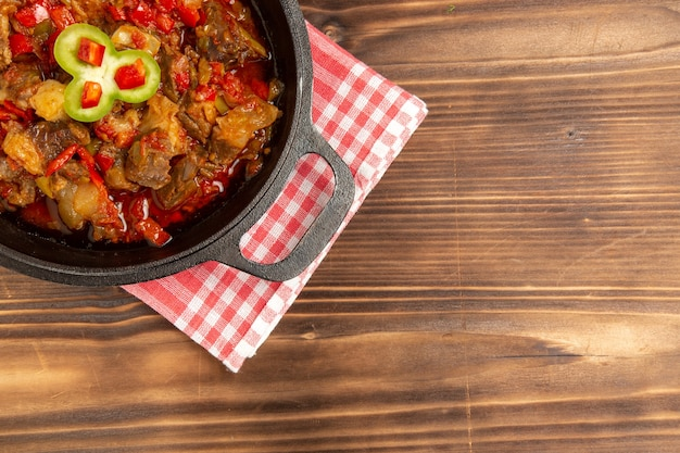 Bovenaanzicht gekookte groentemeel inclusief groenten en vlees binnen op bruin bureau