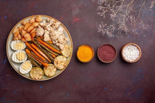 Bovenaanzicht gekookte groenten met eiermeel en kruiden op donkere ruimte