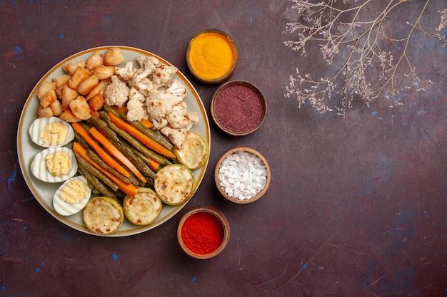 Bovenaanzicht gekookte groenten met eiermeel en verschillende kruiden op donkere ruimte