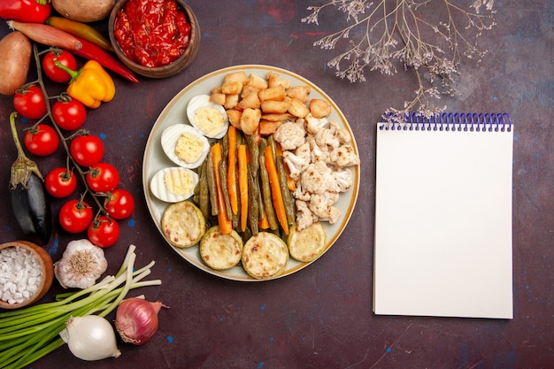 Bovenaanzicht gekookte groenten met eiermeel en verse groenten op donkere ruimte
